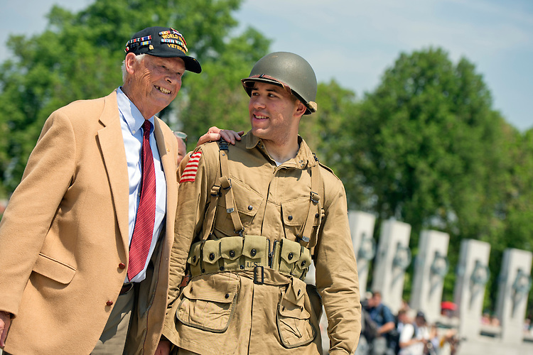 UNITED STATES - MAY 8: WWII veteran Les Jones of San Clemente, Calif., and Army Spec. Tyler Amaker, attend a ceremony at World War II Memorial on the Mall to commemorate the 70th anniversary of the victory in Europe, known as VE Day, May 8, 2015, which featured flyovers by World War II era aircraft. (Photo By Tom Williams/CQ Roll Call)