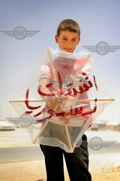 Syrian refugee Faris holds up a kite which he made himself. On the kite is a personal message of peace for his country. Faris was forced to flee Syria with his parents and younger siblings nine and a half months ago. He wanted to express to the world that he misses his homeland, so he painted on his kite 'I miss Syria. Everything there is better' said Faris when remembering his life in Syria. /Felix Features