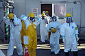 February 20, 2012, Fukushima, Japan - Workers at the damaged Fukushima No. 1 Nuclear power Plant wearing protective suits and masks are seen on their way to work on Feb. 20, 2012 in Okuma, Fukushima Prefecture.