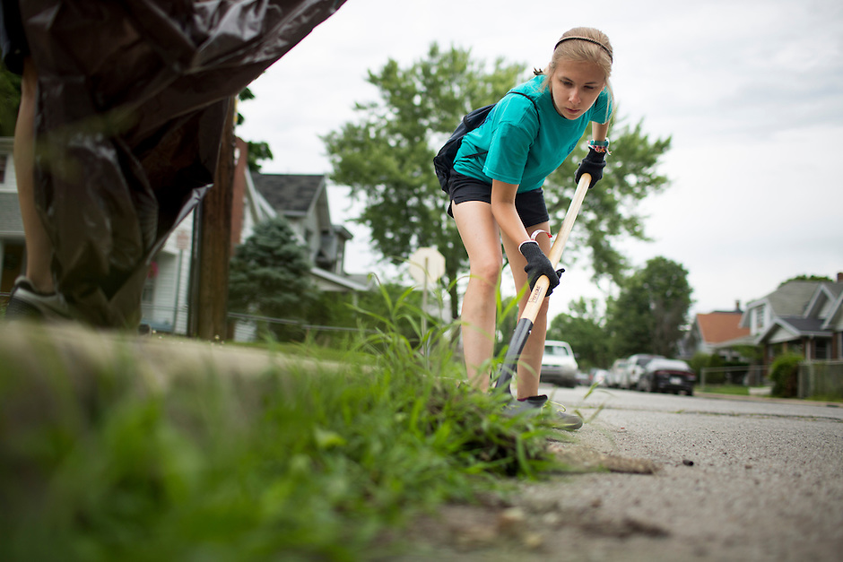 "Sally Finkel uses a shovel to dig up weeds along a curb in the Hawthorne neighborhood during ""Circle the City with Service,"" the Kiwanis Circle K International's 2015 Large Scale Service Project, on Wednesday, June 24, 2015, in Indianapolis. (Photo by James Brosher)"