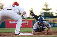 Brian Rike (14) of the Tulsa Drillers slides back into first base during a game against the Springfield Cardinals at Hammons Field on July 19, 2011 in Springfield, Missouri. Tulsa defeated Springfield 17-11. (David Welker / Four Seam Images)