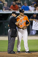 Home plate umpire Grant Conrad explains a call to Greensboro Grasshoppers manager Kevin Randel (26) during the game against the Kannapolis Intimidators at CMC-Northeast Stadium on June 11, 2015 in Kannapolis, North Carolina.  The Intimidators defeated the Grasshoppers 7-6.  (Brian Westerholt/Four Seam Images)