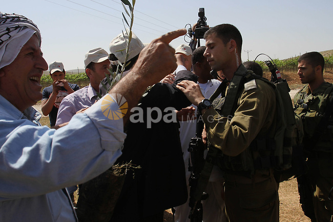 A Palestinian farmer argues with an Israeli soldiers as he prevents farmers from plant olive trees during a protest against what they say is land confiscation for Jewish settlements in the Jordan Valley, a hotly contested part of the occupied West Bank April 8, 2014. Photo by Nedal Eshtayah