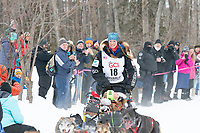 Anna Berington and team run past spectators on the bike/ski trail near University Lake with an Iditarider in the basket and a handler during the Anchorage, Alaska ceremonial start on Saturday, March 7 during the 2020 Iditarod race. Photo © 2020 by Ed Bennett/Bennett Images LLC