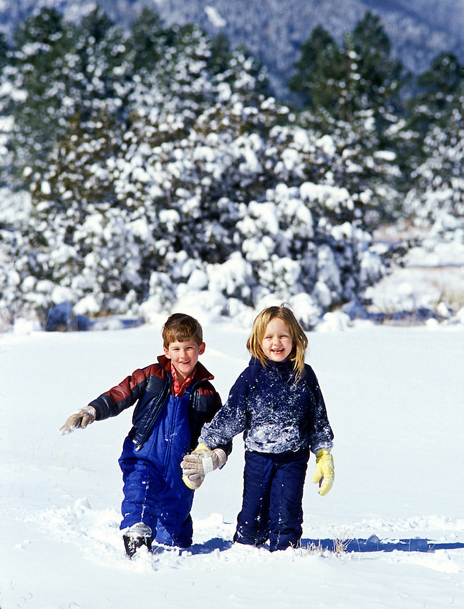 Boy and girl play in new snow after a storm.