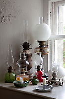 A collection of oil lamps on a window sill. Even after electricity was installed in the castle in the 1970s, Pat Munro's mother, clan chief until 1937, continued to use gas lamps for a year afterwards