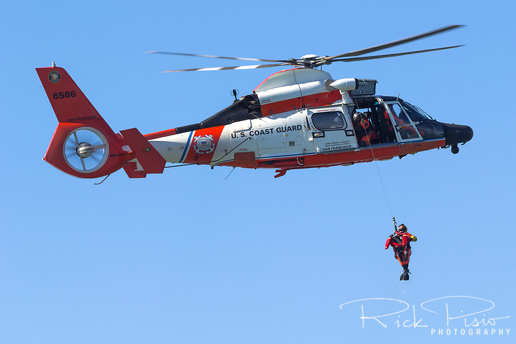 USCG MH-65 Dolphin in heritage paint scheme from Station San Francisco performs hoist operations over San Francisco Bay.