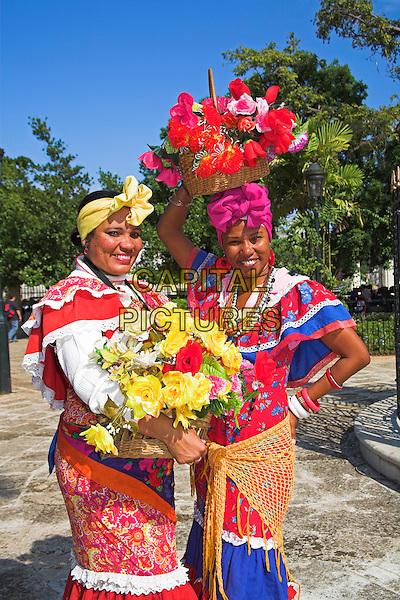 Two women wearing colourful traditional clothing, Plaza de Armas, Havana, La Habana Vieja, Cuba