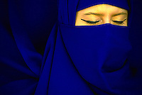 Woman with blue veil covering her face.
