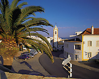 Early morning light on the houses and church of the old town of Albufeira, Algarve, Portugal, partly framed by the leaves of a palm-tree under a deep blue sky