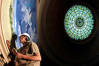 Working atop 35-foot scaffolding, Rick Van Oel of  Evergreene Archictural Art places a few careful touch-up brush strokes upon a newly-installed mural as restoration work continues inside the Dr. Norman E. Borlaug Hall of Laureates in Des Moines.  The four murals are installed directly beneath the building's original rotunda stained glass skylight and pay tribute to Borlaug's life and the programs he created to improve food quality and production worldwide.  Every piece of the stained glass skylight was also cleaned as part of the building's restoration.