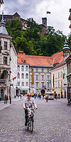 Person cycling in Ljubljana with Ljubljana Castle in the background, Slovenia, Europe
