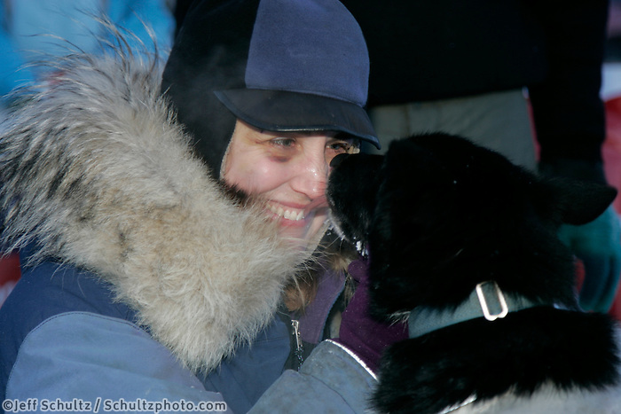 Wednesday March 14, 2007   ----   Ken Anderson's wife Gwen Holdman gives kisses to Ken's lead dogs after they arrived in the finish chute in Nome.  Ken finished the race in 7th place