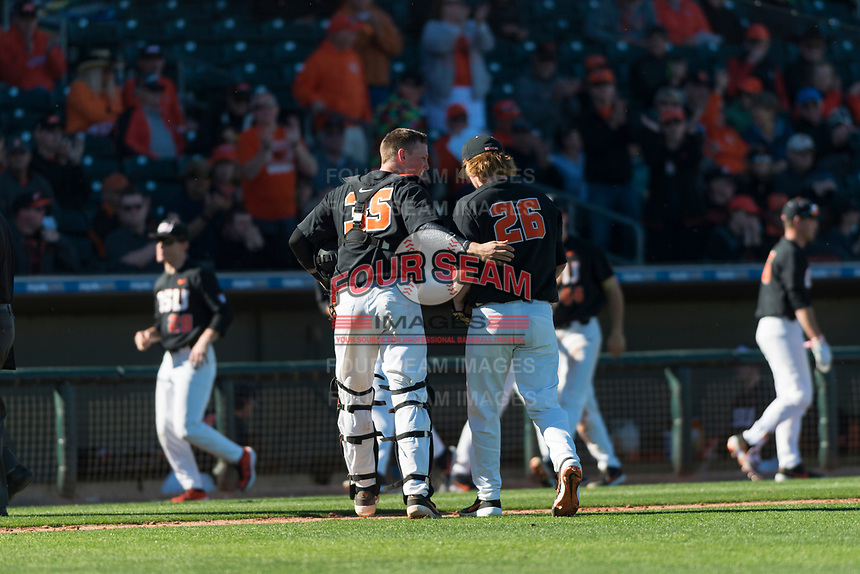 Oregon State Beavers catcher Adley Rutschman (35) congratulates starting pitcher Bryce Fehmel (26) between innings of a game against the Gonzaga Bulldogs on February 16, 2019 at Surprise Stadium in Surprise, Arizona. Oregon State defeated Gonzaga 9-3. (Zachary Lucy/Four Seam Images via AP)