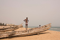 Ghana - Blekusu - Young villagers stand on a traditional fishing boat. <br /> A traditional fishing village, Blekusu lies just beside the sea defence which has been built in the nearby city of Keta. Although the groynes and sea defence wall are now protecting the city from erosion, they prevent sediments from reaching the coastline of Blekusu, resulting in massive erosion of the village coastline
