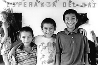 Three young boys attending a community festival. Community of Nueva Esperanza, El Salvador, 1999.