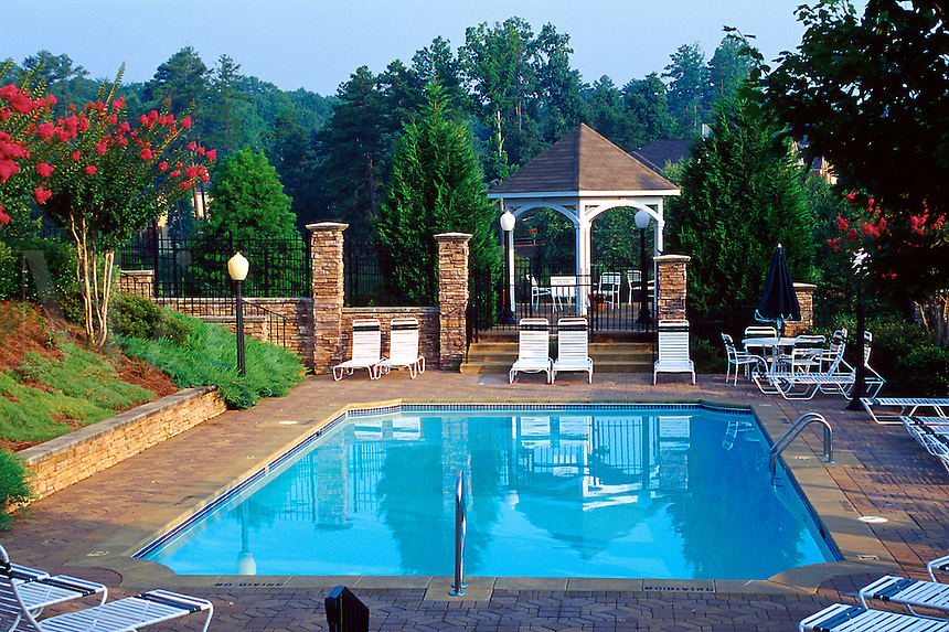 A swimming pool in spring, with blooming crepe myrtle trees as part of the poolside landscaping. Georgia.