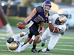 SIOUX FALLS, SD, OCTOBER 8:  Luke Papillion #15 from the University of Sioux Falls is dragged down by Tyshonn Woodard #59 and Kevin Rubin #99 from Southwest Minnesota State University in the first half Saturday night at Bob Young Field. (Photo by Dave Eggen/Inertia)