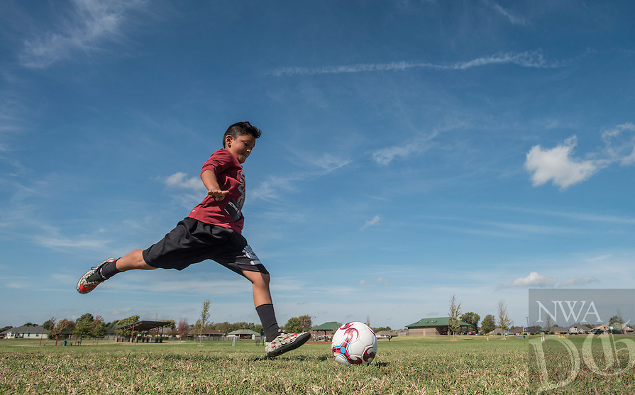 NWA Democrat-Gazette/ANTHONY REYES &bull; @NWATONYR<br /> Angel Sandoval, 10, kicks to ball to his father Tony Sandoval serving as goalie Monday, Oct. 17, 2016 at Ward Nail Park in Lowell. Angel is on fall break and his father took the day off work to practice soccer and spend a little time with his son.