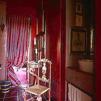 A detail of a red bathroom with red walls and tiled floor. A washbasin stands on a tiled shelf in a recess. A painted chair with a distressed finish stands nearby. A purple and red striped curtain at the doorway provides a vibrant clash of colours.