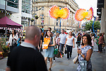 © Joel Goodman - 07973 332324 . 3 August 2013 . Cathedral Street , Manchester , UK . People wander by Gigantic flower sculptures made of balloons and cranes on Cathedral Street . Dig the City urban gardening festival . Photo credit : Joel Goodman