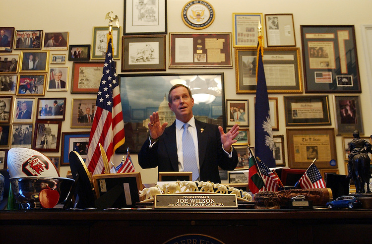 Rep. Joe Wilson, R-S.C., shows of pictures and memorabilia in his Rayburn office.