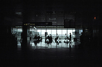 Silhouetted passengers sitting and standing in airport waiting area. Tenerife Sur airport, Tenerife, Spain.