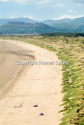 Harlech beach holidaymakers. Gwynedd North Wales UK. Snowdonia National Park in distance.