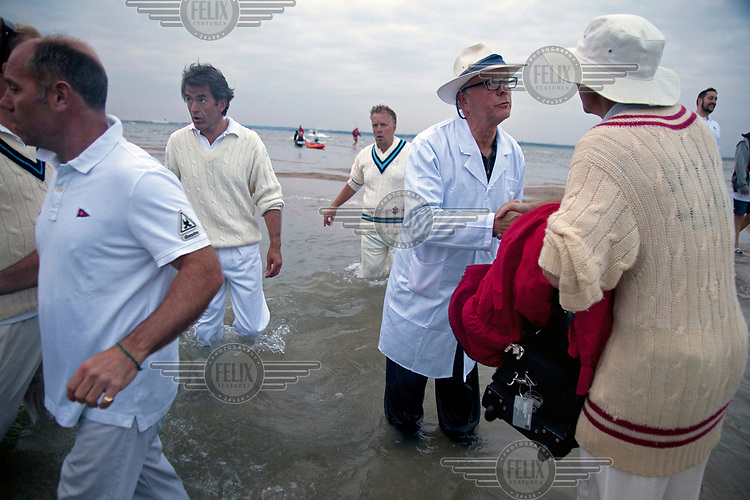 The umpire congratulates a player at the end of the match, ended as water made play impossible, during the annual cricket match held between the Royal Southern Yacht Club and the Island Sailing Club. The match takes place when the bank is exposed at low tide but never lasts very long before the water returns. The undulating surface with large puddles ensures it is more a social occasion than a serious cricket match, and the scoring reflects this, the victor of the game is pre-determined, and the two clubs simply take it in turns to 'win' the match, regardless of play.