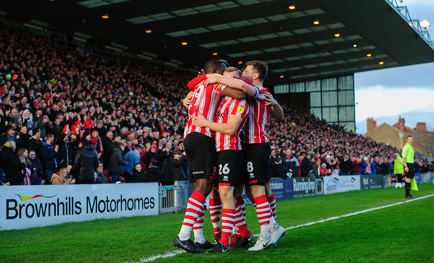 Lincoln City's John Akinde, left, celebrates scoring the opening goal with team-mates<br /> <br /> Photographer Chris Vaughan/CameraSport<br /> <br /> The EFL Sky Bet League Two - Lincoln City v Newport County - Saturday 22nd December 201 - Sincil Bank - Lincoln<br /> <br /> World Copyright © 2018 CameraSport. All rights reserved. 43 Linden Ave. Countesthorpe. Leicester. England. LE8 5PG - Tel: +44 (0) 116 277 4147 - admin@camerasport.com - www.camerasport.com