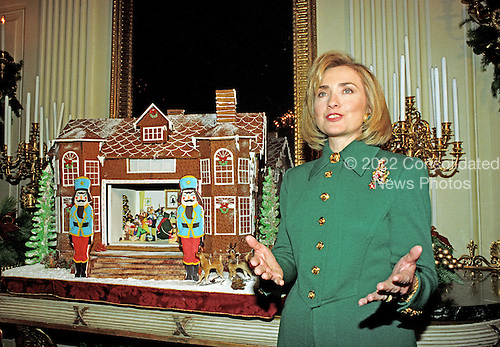 First lady Hillary Rodham Clinton guides members of the press through the White House Christmas decorations in Washington, DC on December 2, 1996.  Here the first lady is photographed with the traditional White House Gingerbread house in the State Dining Room.<br /> Credit: Ron Sachs / CNP