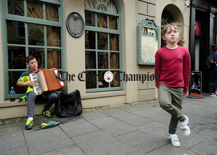 Cormac Mc Colgan of Donegal plays a tune for dancer Ellie Eustace on O Connell street, Ennis during Fleadh Cheoil na hEireann. Photograph by John Kelly.