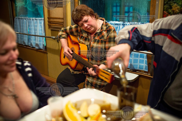 The medical team on board the Matvei Mudrov train celebrates Maslenitsa in the train's dining car, drinking vodka and playing music. Maslenitsa is an eastern Slavic festival which is celebrated to mark the imminent end of winter. <br /> <br /> The Matvei Mudrov train is a medical train operated by Russian Railways along the course of the Baikal Amur Magistral (Baikal-Amur Mainline, or BAM) railway line. Named after a famous 19th century Russian physician, the train employs around 15 doctors who make about 10 trips a year, each lasting two weeks. Along the way they deliver essential medical services to people living in remote villages along the 4,324 km long BAM railway. Though not equipped to carry out surgical procedures the train has heart monitors, ultrasound and x-ray machines to deliver diagnosis.