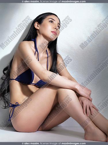 Beautiful Japanese woman sitting on the floor in bikini in artistic dramatic light
