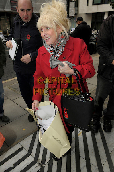 Dame Barbara Windsor .at BBC Radio 2, London, England, UK, .1st November 2012..full length red coat bag postbox handbag shopping leopard print trainers animal scarf .CAP/IA.©Ian Allis/Capital Pictures.