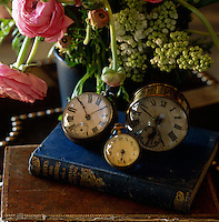 Three antique timepieces sit on top of a pile of books on a side table in the living room