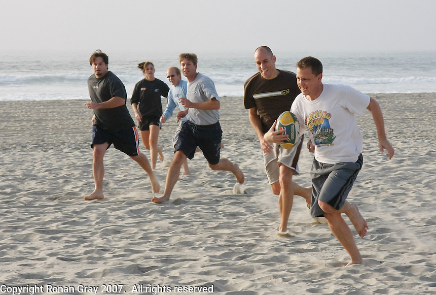 Philip Koekemoer is chased to the try-line in a game of touch-rugby on Mission Beach, San Diego, California November 18 2007.  Philip and fellow South Africans (from R) Greg, Cobus and Ian plus Americans Ruthie and Keith play each Sunday on South Mission Beach.  South Africa are the current Rugby World Cup champions having won the competition in France on October 20, 2007.  They will hold the title until the next World Cup Competition is played in New Zealand in 2011.