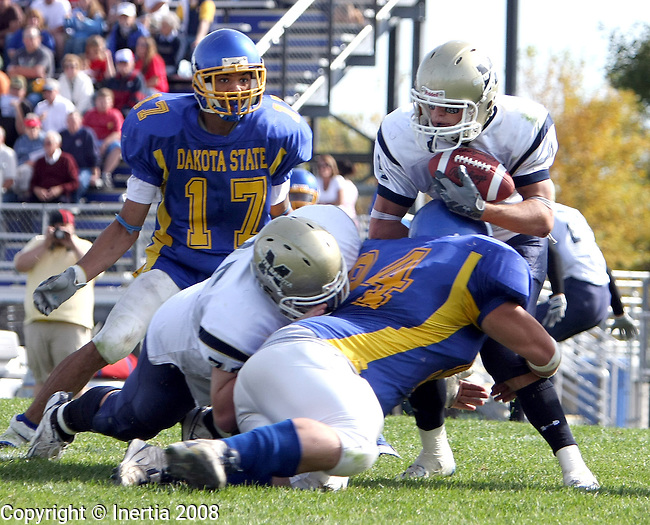 MADISON - SEPTEMBER 27: Jamie Dale #4 of South Dakota Tech is hit and brought down in the backfield by Chris Schiller, #94 of Dakota State University for a safety in the fourth quarter Saturday afternoon Trojan Field in Madison. (photo by Schyler Eggen/Inertia)