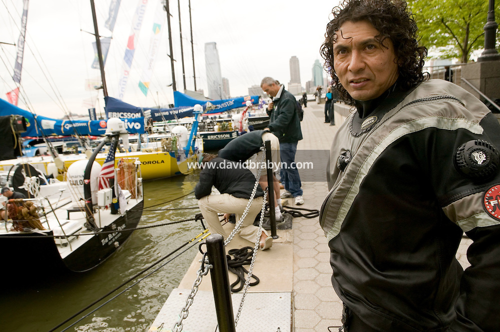9 May 2006 - New York City, NY - Diver Edward Moreno (R) joins team members after having checked the hulls of yatchs moored at the North Cove Marina in New York City, USA, between two legs of the 32,700 nautical miles-long Volvo Ocean Race. A local commmercial diver, he has been hired by the teams to look after the yatchs' hulls that do not have a protective coating in order to increase speed. Photo Credit: David Brabyn