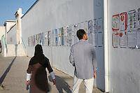 23 ottobre 2011 Tunisi, elezioni libere per l'Assemblea Costituente, le prime della Primavera araba: un uomo e una donna camminano accanto a un muro dove sono appesi i cartelloni elettorali dei vari partiti candidati.<br /> premieres elections libres en Tunisie octobre <br /> tunisian elections