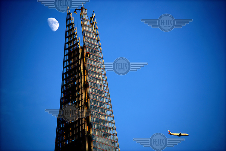 The moon visible beside the peak of the Shard rising from London Bridge. It is Western Europe's tallest building at 310 metres. To the right a British Airways passenger aeroplane flies towards Heathrow Airport.