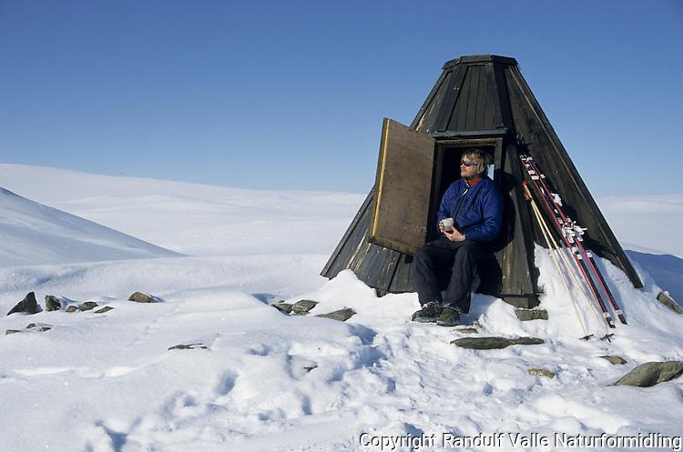 Mann sitter i døråpning på hytte og drikker kaffe ---- Man sitting in the door of a cabin, drinking coffe