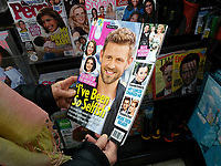 A reader browses a copy of Us Weekly magazine at a newsstand in New York on Wednesday, March 8, 2017. Tronc, the publisher of the LA Times and Chicago Tribune is reported to be in talks with Wenner Media to acquire Us Weekly, the celebrity magazine. (© Richard B. Levine)