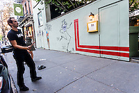 """New York, NY 18 September 2015 - French Graffiti artist L'Atlas at work on a mural. His """"abstract calligraphy"""" creats a strong contrast to the work of French graffiti artist JR and Brasilian twins, Os Gemeos, whose work appears on the right. ©Stacy Walsh Rosenstock"""