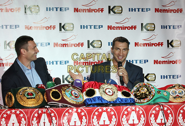 Vitali Klitschko, Wladimir Klitschko.Press conference in Kiev, Ukraine..July 7th, 2011.half length black suit jacket white blue shirt table sitting microphone profile .CAP/PER/VV.©VV/PersonaStars/CapitalPictures