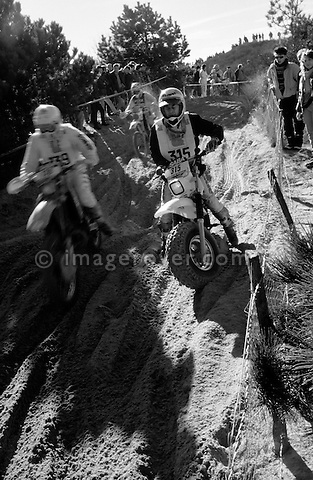 Enduro du Touquet 1988. Dirt bike beach race at Le Touquet, Normandy, France. --- No releases available, but releases may not be necessary for certain uses. Automotive trademarks are the property of the trademark holder, authorization may be needed for some uses. --- Info: A thousand motorcycles take part in this mad event. The race starts along the beach, followed by a run into the sand dunes. The entry point in the dunes is most spectacular: All motorbikes have to pass through a small opening in the dunes. Once the fast professional drivers have flown through, this first passage developes into a true bottleneck with many hundreds of motorbikers trying to get through at the same time. Motorcycles are strewn all over the place. Many have fallen, others have already broken down. In the meantime, the professional riders are progressing quickly. But their riding style changes from racing full-out as soon as they are approaching the lappers from behind. Outmaneuvering them at high speeds is an art form! After three hours it's all over.....