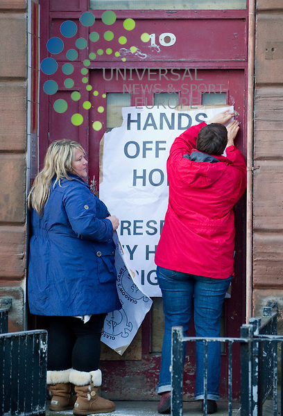 Supporters put up protest signs. Jack and Margaret Jaconelli have barricaded themselves within their Dalmarnock home in a dispute over a compulsory purchase order issued on behalf of Glasgow City Council. Sheriffs Officers were expected to arrive today to enforce the eviction but as of 6pm had not appeard on 21 March 2011, Picture: Al Goold/Universal News and Sport (Europe) 2011.