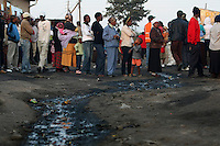 People stand in a long line outside a polling station in Diepsloot, Johannesburg waiting to cast their votes in the 2009 general election.
