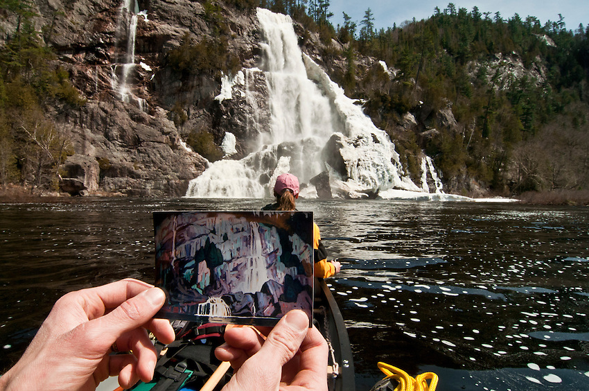 Writer Conor Mihell holds a small painting of Bridal Veil Falls done by a member of the Group of Seven in front of the actual Bridal Veil Falls on the Agawa River of Ontario Canada.