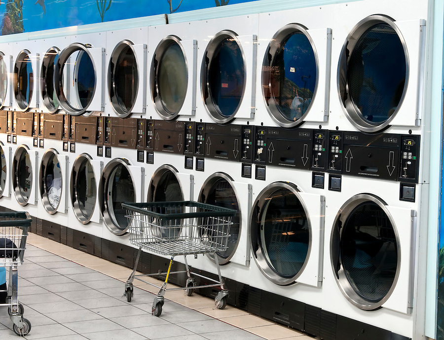 View of row of washer and dryers in commercial laundry shop.